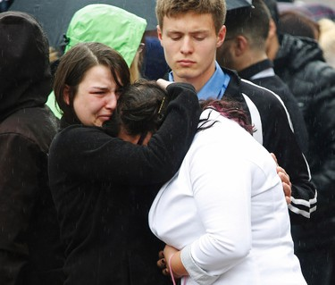 Young people console each other following the funeral service for 17-year-old Rehtaeh Parsons outside St. Mark's Anglican church in Halifax, Nova Scotia, April 13, 2013. Parsons, a local high school student, was taken off life support on April 7, three days after she tried to hang herself. The teen was bullied for more than a year after an alleged sexual assault which happened when she was 15, her family said.  REUTERS/Paul Darrow