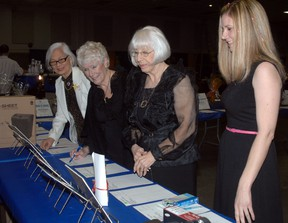 Friends Carol Aragon, left to right, Frances Gottschlich, Alma Yates, and Lisa Dennis look at items up for grabs in the Woodstock and District Developmental Services silent auction during the Woodstock/Oxford Rotary Fish Fry Saturday, April 13, 2013.  (TARA BOWIE, Sentinel-Review)