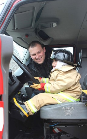 Photo by Jeannette Benoit  Kalen Garnett takes the opportunity to sit in the driver's seat of a fire truck at the first Get Outdoors Weekend, put on by the Vermilion chapter of Be Fit For Life. Although the weather was a bit chilly, many people joined to take part in an array of outdoor activities at the event Saturday afternoon.