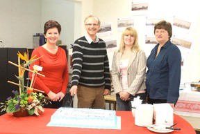 Ad Sales Rep Charlotte Smith, Town Councilor Rob Pulyk, Editor Jeannette Benoit, and Customer Service Rep. Dixie Zizek cut the cake.