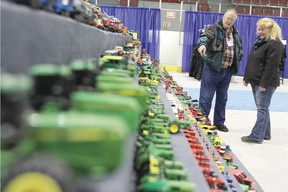 Frank Douglas, left, shows of his collection of toy tractors and farm equipment to Carol Ashton which were on display in the Ag Hall at the Trade Show April 13. Douglas has been collecting for the last 30 years.