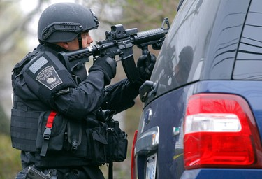 A member of the SWAT team trains a gun on an apartment building during a search for the remaining suspect in the Boston Marathon bombings in Watertown, Massachusetts on April 19, 2013. (REUTERS/Jessica Rinaldi)