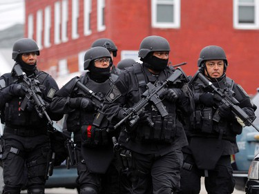 WIRE PHOTOS OF THE WEEK APRIL 19--SWAT teams enter a suburban neighborhood to search an apartment for the remaining suspect in the Boston Marathon bombings in Watertown, Massachusetts April 19, 2013. Two Boston bomb suspects were named as brothers, Dzhokhar A. Tsarnaev, 19, and his brother Tamerlan Tsarnaev, 26, a U.S. national security official said on Friday. The official said the older brother died in a shootout with police and the younger one was being sought in a house-to-house search for in the Boston suburb of Watertown. REUTERS/Jessica Rinaldi