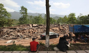 People sit near collapsed buildings after a strong 6.6 magnitude earthquake, at Longmen village, Lushan county, Ya'an, Sichuan province, April 20, 2013. The earthquake hit a remote, mostly rural and mountainous area of southwestern China's Sichuan province on Saturday, killing at least 102 people and injuring about 2,200 close to where a big quake killed almost 70,000 people in 2008. REUTERS/Stringer