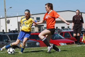 DARRYL G. SMART, The Expositor  BCI's Jenna Schonbacher tries to get past NPC defender Megan Phillips during Brant County high school girls soccer action Monday at WIFO Park in Paris.
