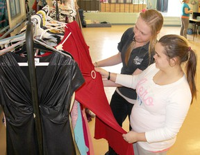 Students Martha Friesen, 18, left,  and Vanessa Haskell, 17, admire one of the $20 prom dresses for sale at the Ursuline College Chatham Dress Drive in Chatham, Ontario on Thursday, April 25, 2013. (VICKI GOUGH/ THE CHATHAM DAILY NEWS/ QMI AGENCY)