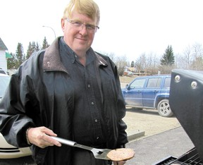 Mayerthorpe Mayor Kim Connell grills burgers on the sidewalk beside the Community Services Building in Mayerthorpe. The barbecue from 11 a.m. to 2 p.m. on Wednesday, April 24, is an annual event held to honour the town's volunteers.