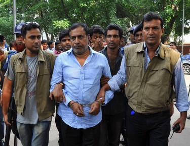 """Members of the Detective Branch of Police escort Abdul Khalek, the father of Mohammed Sohel Rana, to their custody after his arrest in Dhaka April 29, 2013. Bangladeshi lawyers and protesters chanted """"hang him, hang him"""" on Monday as the owner of a factory building that collapsed last week killing nearly 400 people was led into court dressed in a helmet and bullet-proof jacket, witnesses said. Eight people have been arrested - four factory bosses, two engineers, building owner Mohammed Sohel Rana and his father, Abdul Khalek. Police are looking for a fifth factory boss, David Mayor, who they said was a Spanish citizen. (REUTERS/Stringer)"""