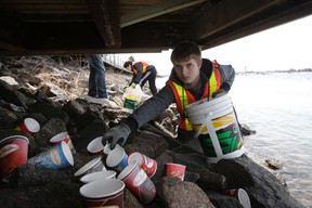 Clean North volunteer Alex Ross gathers discarded coffee cups under the boardwalk on the St. Marys River recently. The annual shoreline garbage collection was postponed for several weeks due to the snowy conditions. Over the winter, rubbish collects between the boardwalk and the river, making a mess when the snow melts in spring.