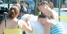 Karma Restaurant and Pizzeria owner Mike Saunders is comforted by, from left, Tammy Raycraft, wife and restaurant co-owner Sherry Saunders and Payton Huff following a fire in the business Thursday afternoon in downtown Stratford. (SCOTT WISHART, The Beacon Herald)