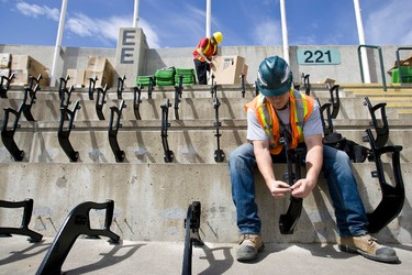 Adans Henderickson installs bolts on seat mounts during  the installation of new seats at Commonwealth Stadium in Edmonton, Alta., on Thursday, May 2, 2013. Seats in the upper bowl are being replaced ahead of the start of the CFL season; for the Edmonton Eskimos, their season begins on June 14 at home against the Saskatchewan Roughriders. Ian Kucerak/Edmonton Sun/QMI Agency
