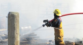 A Mayerthorpe firefighters sprays flames in the yard of a rural property about 16 kilometres north of Mayerthorpe at about 5 p.m. on Sunday, May 5.