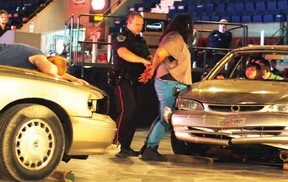 Students act out a simulated car crash —including an arrest for impaired driving — along with police, firefighters and paramedics, during Safe Grad 2013 at the civic complex on Thursday. Staff photo/CHERYL BRINK