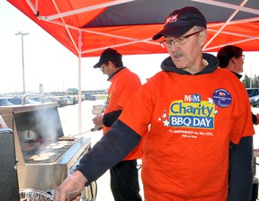 Volunteers Byron Turcotte, right, serves up a hamburger while behind him Wayne Harris cooks up some more, during the M&M Meat Shop Charity BBQ Day at the Portage la Prairie Mall Saturday. The event raised money for the Crohn's and Colitis Foundation of Canada. Turcotte's daughter has Crohn's while Harris has a connection to the food store. (CLARISE KLASSEN/PORTAGE DAILY GRAPHIC/QMI AGENCY)