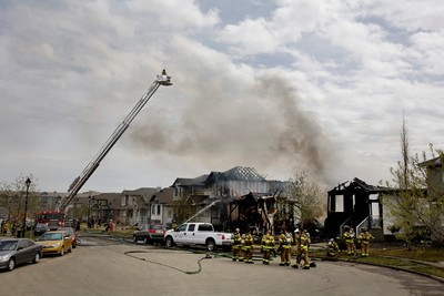 Firefighters put out hotspots on a blaze that destroyed three homes in a cul de sac in Lewis Estates, at 213 Street and 87 Avenue in Edmonton, Alta. on Sunday, May. 12, 2013. Two other homes had melted siding and no-one was injured in the blaze. Amber Bracken/Edmonton Sun/QMI Agency