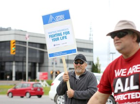 Frontenac paramedics protest cuts to service at the intersection of Gardiners Road and Princess Street on Saturday. (Danielle VandenBrink/The Whig-Standard)