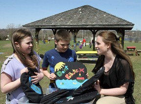 Student teacher Amanda Morgan and Grade 5 students Ethan Lucas and Annabella Branscombe store pillows decorated with environmental themes by Grade 5 students.        ROB MOOY - KINGSTON THIS WEEK