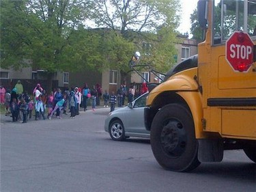 Children wait for school buses a few doors down Ritchie St. from the scene of a fatal shooting late Tuesday, May 14. (DANIELLE BELL Ottawa Sun)