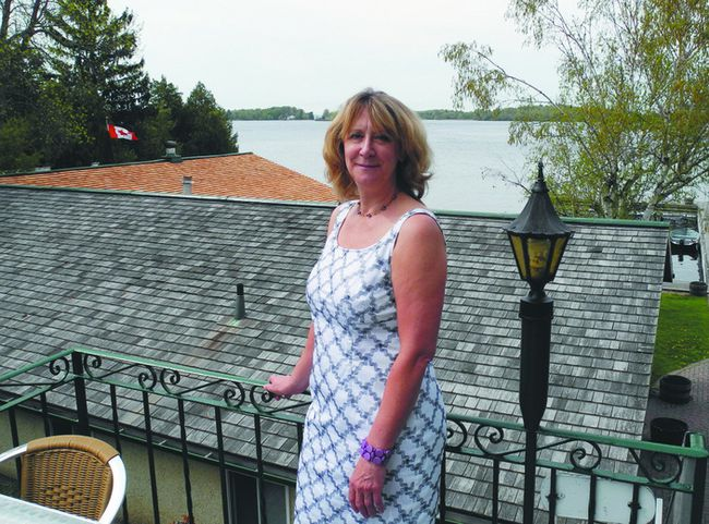 Katherine Christensen of the TIAP stands on a deck of the Gananoque Inn after announcing the island contest. Behind Christensen, just to the left of her head, is the island in the contest.