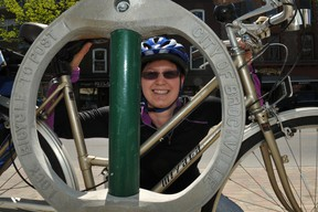 Kathleen Lowe, of Brockville's cycling advisory committee, places her bicycle by one of the bike parking rings placed on King Street to lure more cyclists downtown. RONALD ZAJAC The Recorder and Times
