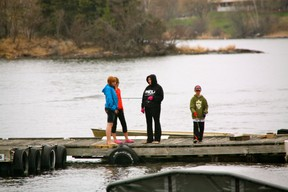 A group of children fish on the Harbourfront during a rainy opening weekend.