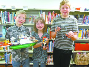 Three of the four winners of the Mayerthorpe Public Library Lego Contest show their prize-winning creations on awards day Wednesday, May 10. William McDowell, the Fan Favourite with The Ship, Laura Jager, in the ages seven to nine category, with her Robot Garbage Taker, and Treyton Mason, in the ages 10+ category, with his Champ and Squat. The prizes? More lego.