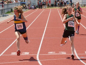 Delhi District Secondary School's Alexa Leitch outreaches Alex Girardi from Brantford's St. John's College during a midget girls 400 metre heat Wednesday at Day 1 of the Central Western Ontario Secondary School Association track and field championships at Jacob Hespeler Secondary School in Cambridge. DARRYL G. SMART QMI Agency