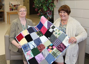 Karen Lambert (right) of the Alzheimer's Society presents a 'touch quilt' to Margaret Warner, a social worker at Lions Prairie Manor in Portage la Prairie. The North Central Region office has received quilts donated by Fairholm and Elm River Hutterite Colonies which they have in turn donated to long term care facilities in the area. Touch quilts are made of different colours and textures of fabric with added pieces like zippers, buttons, and strings to enhance touch and comfort. (SUBMITTED PHOTO)