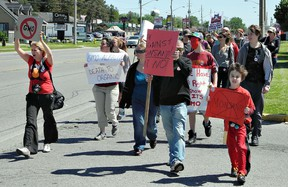 Rachel Higgins (left) leads a stream of people up King George Road on Saturday as part of a march to raises awareness about genetically modified organisms in food. (HUGO RODRIGUES, The Expositor)