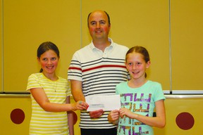 Holy Cross School Grade 6 students Cailyn Poole (left) and MacKenzie Gill (right) present  Habitat for Humanity Director of Family Services Armand Mercier with a cheque for $1,263, raised in a Lenten social justice endeavour.