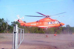An Ornge air ambulance helicopter kicks up some dust as it lands at a temporary helipad on Bethel Lake Court on Monday evening for the first time. Helicopters are expected to begin flying in and out of the field  for six to eight weeks while the permanent helipad at Ramsey Lake Health Centre is repaired. GINO DONATO/THE SUDBURY STAR