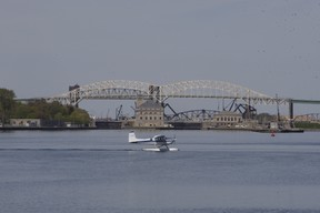 A float plane drifts past the International Bridge on the St. Marys River on Monday. The river between the twin Saults has been increasing in traffic as the seasons drift from spring towards summer.