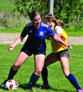 Kaila Burton, of St. Mary (blue jersey) eyes making a pass under pressure from Olivia Proctor of ADHS during high school girls double-A soccer action earlier this month. The Crusaders girls had a spectacular season this spring, going all the way to the EOSSAA final, where they were defeated 1-0 on penalty kicks by Perth's St. John Spartans. (RECORDER AND TIMES FILE PHOTO)