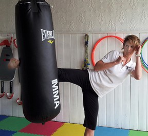 Twilight Fitness owner Christina Outingdyke-Ellis shows off her muay thai skills at the Grand Opening.