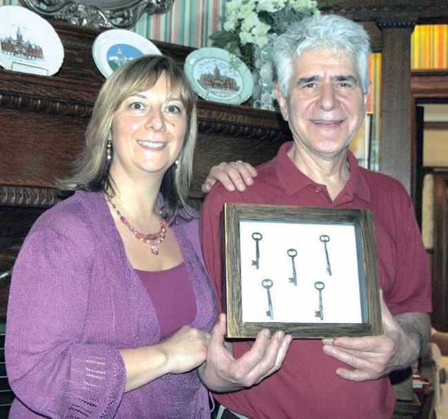Elena Pastura and Dom Tassielli hold the original keys to Birmingham Manor, now a Bed and Breakfast, Saturday during Doors Open. The house was built in 1905 by John L. Youngs, the same builder who constructed City Hall and St. Andrew's Presbyterian Church. (LAURA CUDWORTH, The Beacon Herald)