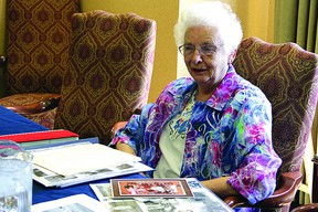 Beatrice Bodell, 87, looks over photos of her family while recounting her life in Strathcona County. Leah Germain/Sherwood Park News/QMI Agency