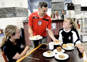 Owner Sean Muharrem serves food to two students at the new Grand Castle Cafe, while co-owners Margery and Dean Muharrem and chef Jeff Ramboer work the counter in the background. DIANA MARTIN/ THE CHATHAM DAILY NEWS/ QMI AGENCY