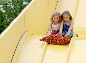 Four-year-old Chloe Vadovic, left, and her twin sister, Karissa, go for a slide at the Kinsmen Fair on Sunday. TREVOR TERFLOTH/ THE CHATHAM DAILY NEWS/ QMI AGENCY