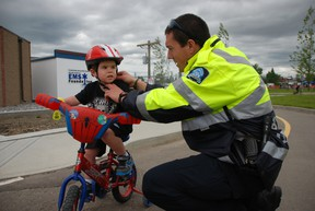 Peace officer Catlin Chiasson, right, helps four-year-old Connor Balcom tighten his helmet before trying out the bicycle safety training course at Grande Prairie's Safety City during the fourth annual Devon Safety Expo. Peace officers like Chiasson were on hand to help children learn proper hand signals and the rules of the road for when they take their bikes out over the summer. JOCELYN TURNER/DAILY HERALD-TRIBUNE/QMI AGENCY