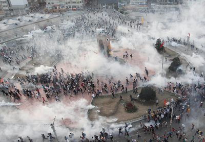 Protesters run as riot police fire teargas during a protest at Taksim Square in Istanbul June 11, 2013. Turkish riot police fired volleys of teargas canisters into Istanbul's Taksim Square, centre of protests against Prime Minister Tayyip Erdogan, driving thousands into narrow side streets, witnesses said.    REUTERS/Osman Orsal