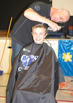 Students and adults alike shaved their heads for Cops for Cancer at Ripley-Huron Community School on June 6, 2013.  Grade 8 student Riley Kirkpatrick gets his head shaved by his Dad Mike. (ALANNA RICE/KINCARDINE NEWS)