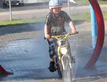 Joey McLennan, 6, rides his bike through the splash pad at O'Connor Water Park in Sudbury, ON. on Friday, June 14, 2013. JOHN LAPPA/THE SUDBURY STAR/QMI AGENCY