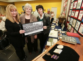 Lori Oschefski, Gloria Phillips and Sandra Joyce hold up a photo of an early group of Barnardo Boys shipped to Canada in 1882. The three women were presenters at the Owen Sound and North Grey Union Library in Owen Sound on Saturday, June 15, 2013 for a seminar on the history of the British Home Children.  (JAMES MASTERS/QMI Agency/The Sun Times)