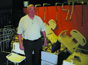 Ken Stewart stands amid the clutter of medical equipment that he collects, fixes and distributes to the needy. Stewart has been awarded the Governor General's Caring Canadian award for his volunteer activities.          Wayne Lowrie - Gananoque Reporter