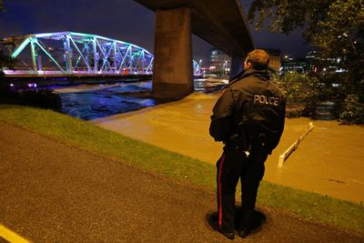 Police officer patrols the bike path along the Bow River by Langevin Bridge in downtown Calgary, Alberta, on June 20, 2013. Mike Drew/Calgary Sun/QMI AGENCY