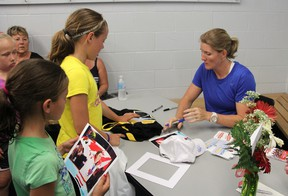 Four-time Olympic medalist and women's hockey ambassador Hayley Wickenheiser signs autographs at the Point Edward Arena, Sunday. Wickenheiser met with local youth, including members of the Sarnia Junior Lady Sting Atom C team, who won the provincial championships last year, coached by Erin White. The visit was the result of a winning contest entry from teammate Tori Iacobelli. (TARA JEFFREY, The Observer)