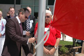 Former patients Brett Batten and Bill Lee raise a flag Friday during the official opening of the new Southwest Centre for Forensic Mental Health in St. Thomas.