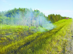 Mayerthorpe firefighters work to put out this grass fire in Lac Ste. Anne County on Highway 22 about seven miles south of town.