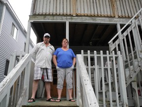 Brian Lalonde and Deborah Mulley on the back porch of their Easton Street apartment. They wants repairs made to where they live, and after making complaints to the city, a meeting is set for today between the landlord and bylaw officials. KATHRYN BURNHAM staff photo