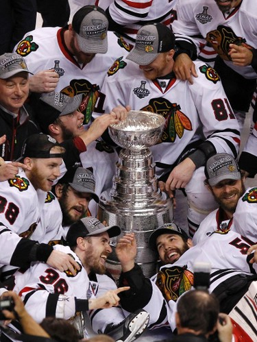 Chicago Blackhawks players and coaches celebrate with the Stanley Cup after they defeated the Boston Bruins in Game 6 of their NHL Stanley Cup Finals hockey series in Boston, Massachusetts, June 24, 2013. (REUTERS/Adam Hunger)